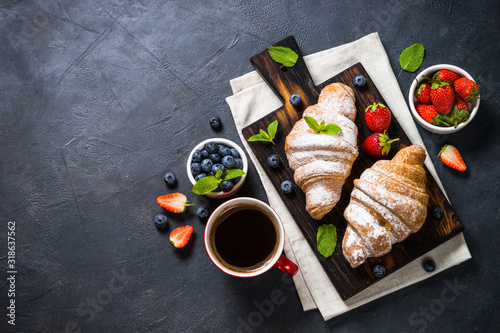 Fototapeta Croissant with fresh berries and cup of coffee on black. obraz