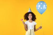 Cute Little Girl With Party Hat Holding Balloon Isolated On Yellow Background