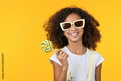 Obraz Smiling little girl in sunglasses holding lollipop isolated over yellow background - fototapety do salonu