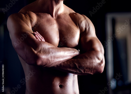 Strong, fit and sporty bodybuilder man over black background. Canvas Print
