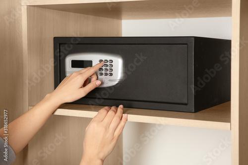 Fototapeta Woman opening black steel safe with electronic lock at hotel, closeup obraz