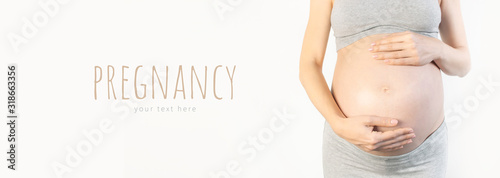 Beautiful young pregnant woman holds hands on her belly on white background Fototapet