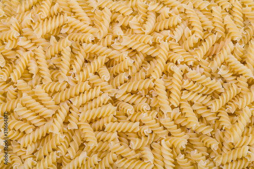 Obraz Raw dried extruded fusilli pasta texture. Staple food of Italian cuisine. Culinary background from short uncooked helical pastas for cooking side dishes. Use for recipe, packaging design, gastronomy. - fototapety do salonu