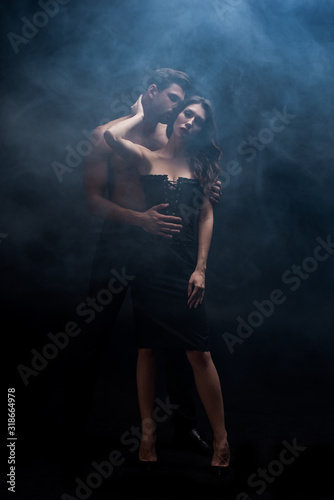 Full length of muscular man kissing sexy woman on black background with smoke Fototapete