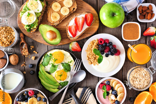 Obraz Healthy breakfast table scene with fruit, yogurts, smoothie bowl, oatmeal, nutritious toasts and egg skillet. Above view over a wood background. - fototapety do salonu