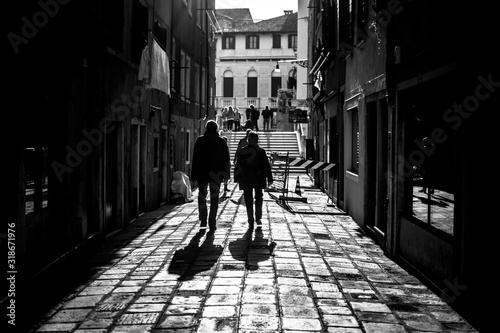 Photo Grayscale shot of two men walking down an alley casting shadows on the foregroun