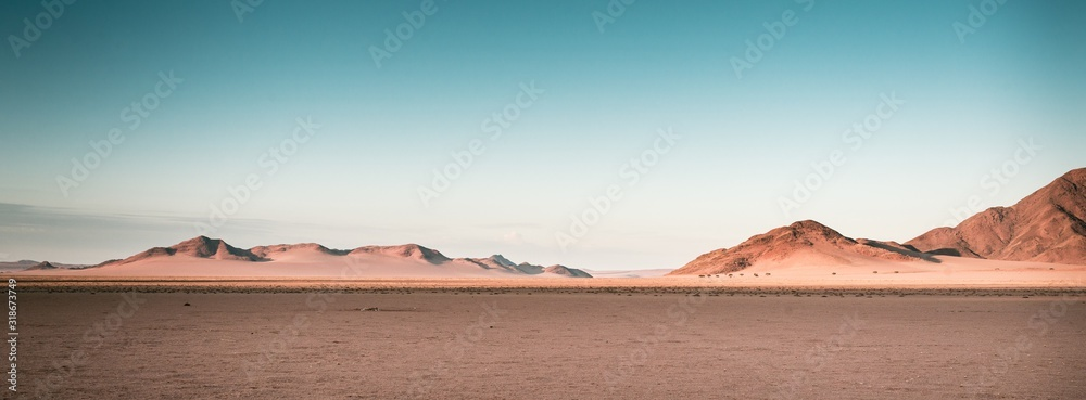 Fototapeta Breathtaking panoramic shot of desert plains in Namibia Africa with hills in the background