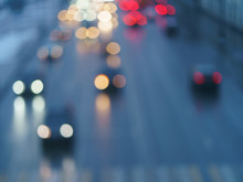 Defocused Photography Of Lights On The Cars In Move On The City Street In Night. Road Is Filled By Cars. Suitable As Template And Background For Postcards, Greeting Cards.