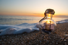 Small Sailing Ship In A Bottle At Sea With Beautiful Sunset