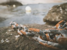 Closeup Shot Of Rusty Metal Chain On A Rock With The Sea In The Background