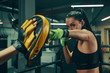 Leinwanddruck Bild - Athletic woman during fight training on boxing ring wearing green bandages on hands, punching exercises with coach
