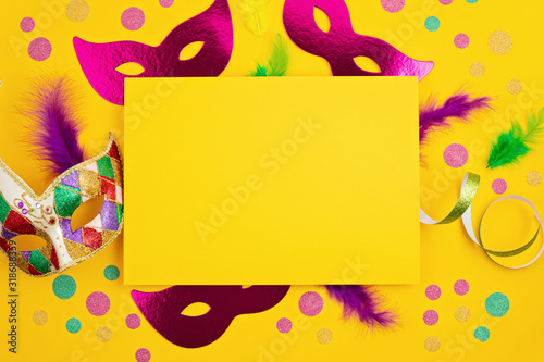 Fototapeta Festive, colorful mardi gras or carnivale mask and accessories over yellow background. Party invitation, greeting card, venetian carnivale celebration concept. Flat lay, top view, copy space obraz