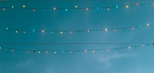 Low Angle View Of Illuminated Light Bulbs Hanging Against Blue Sky During Dusk