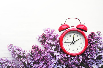 Red alarm clock and bouquet of pink lilacs on a white surface, top view. Hello spring, spring time, conceptual image