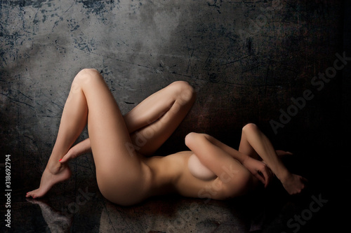 Fotomural Side View Of Naked Woman Lying Against Wall