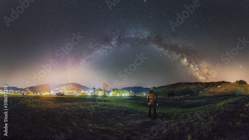 Photo Person looks at the night sky with a milky way near the city