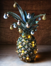 Close-Up Of Illuminated Pineapple With Baubles On Table