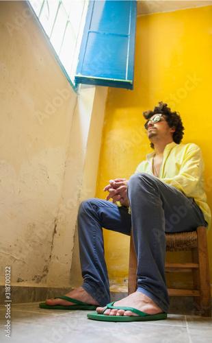 Billede på lærred Man Sitting On Stool At Home