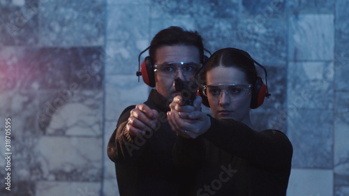 Cuadros en Lienzo A man teaches a woman how to shoot a gun indoors pistol speed firing girl police