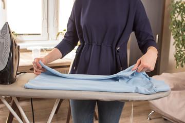 Kobiece dłonie składają wyprasowaną koszulkę leżącą na desce do prasowania. Żelazko stoi na stopce na desce do prasowania. Obowiązki domowe.