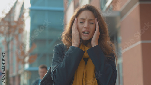 Obraz na plátně Portrait young woman stand with headache look at camera sneezing feel sick at ou