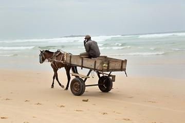 Hombre en carro por la playa.