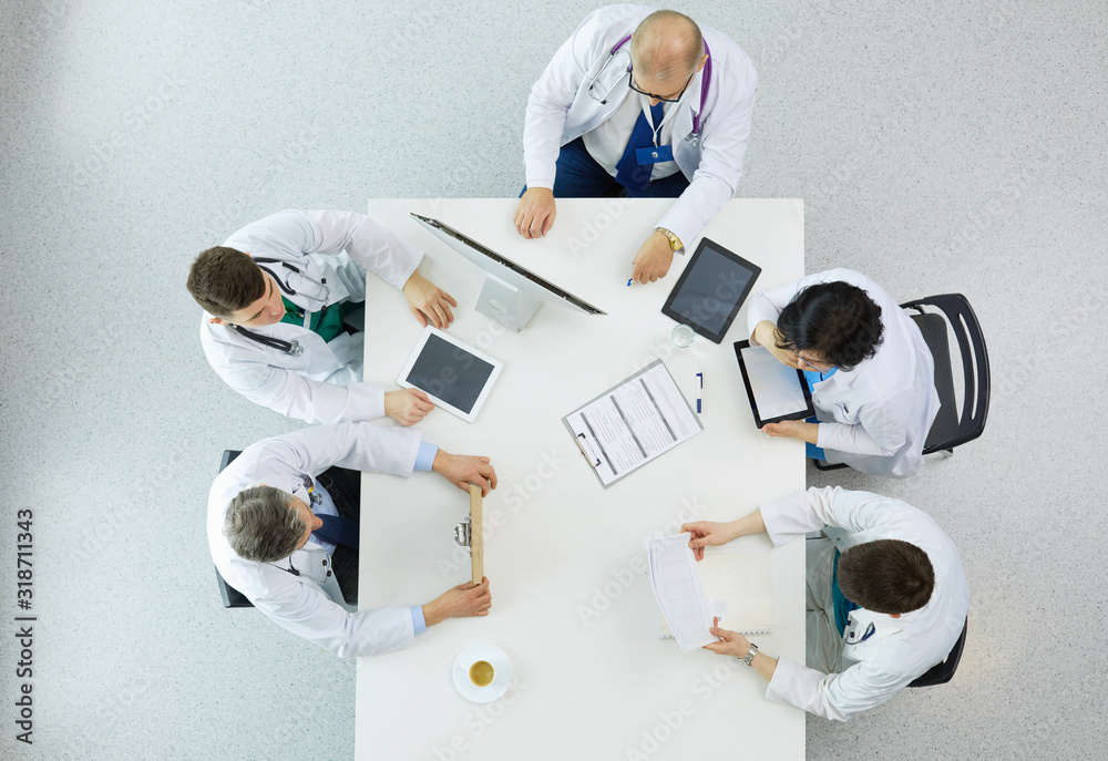 Fototapeta Medical team sitting and discussing at table, top view