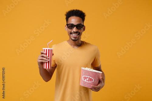 Платно Smiling young african american guy in 3d imax glasses posing isolated on yellow orange background