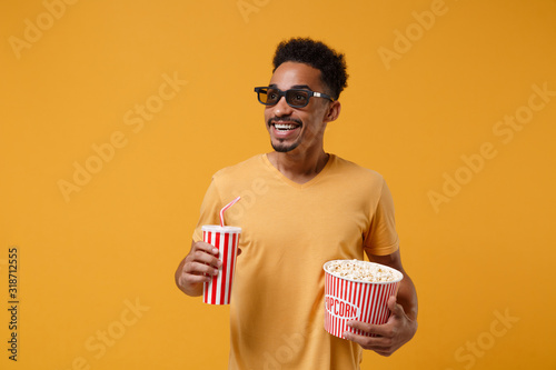 Smiling young african american guy in 3d imax glasses posing isolated on yellow orange background Canvas Print