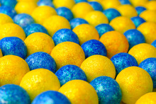 Many Of Bright Blue And Yellow Balls Lying In Row Diagonally. Multi Colored Ball In Colors Of Ukrainian Flag. Selective Focus.