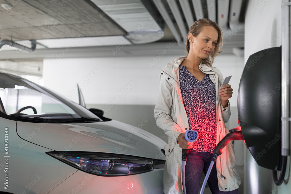Fototapeta Young woman charging an electric vehicle in an underground garage equiped with e-car charger. Car sharing concept.