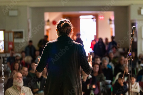 Rear view of female giving motivational speech while standing by mike on stage against audience in auditorium with focus on foreground