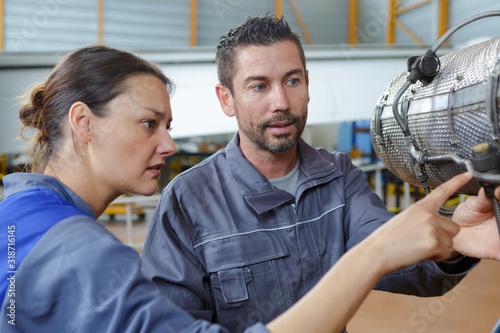 mechanics in aircraft hangar examining dismantled part