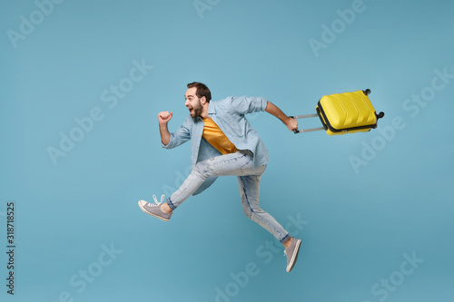 Tela Side view of funny traveler tourist man in yellow clothes isolated on blue background