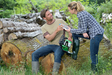 Woman Giving Water Bottle To Tree Logger