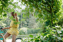 African American Woman Riding Bike On Tennis Court During Summertime