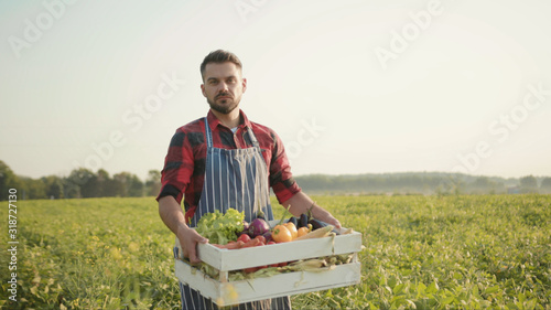 Close up handsome farmer is holding a box of organic vegetables walk look at camera at sunlight agriculture farm field harvest garden nutrition organic fresh outdoor slow motion