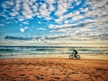 Side View Of Man Cycling At Beach Against Cloudy Sky