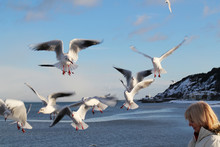 Birds Flying Over Woman Against Sky