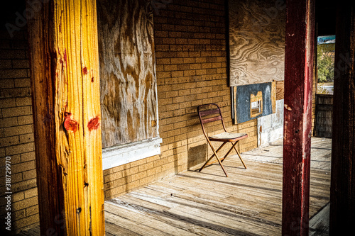 Photo empty chair on porch of abandoned boarded up house