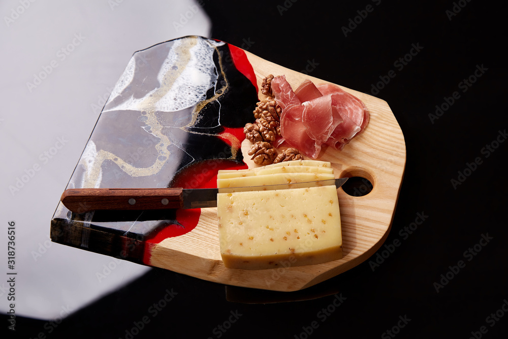 Exclusive painted art cutting board made of wood organic serving dishes with taste food cuisine delicious cheese jamon jerky meat nuts.