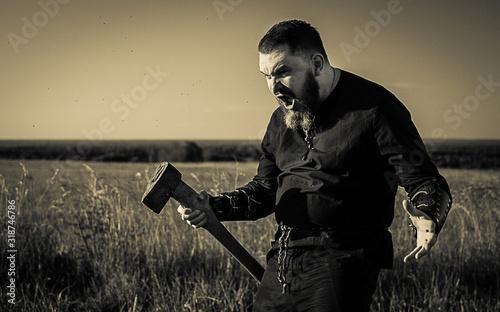 Fototapeta Angry Hunter Holding Axe On Grassy Field Against Sky