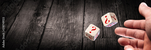 Fotomural Hand Throwing Two Dice With Red Question Marks Onto Wooden Table