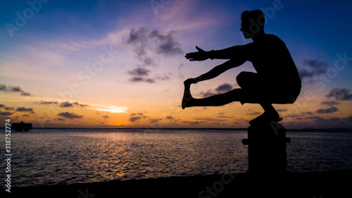 Fotomural Silhouette Man Exercising On Bollard By Sea During Sunset