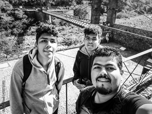 Portrait Of Smiling Friends Standing On Footbridge During Sunny Day