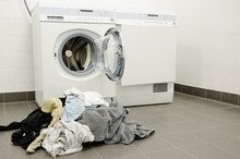 Heap Of Clothes By Washing Machine At Home