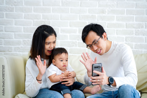 Happy Asian family making a video call at home Fototapeta