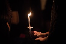 Close-Up Of Woman Holding Lit Candles At Church