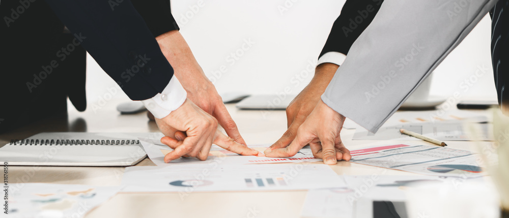 Fototapeta hands and fingers of businesspeople pointing at one point on meeting table in concept of aiming together on same business target