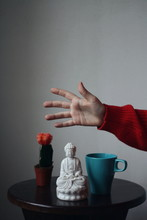 Close-Up Of Hand With Coffee Cup And Buddha Figurine On Table Against Gray Background